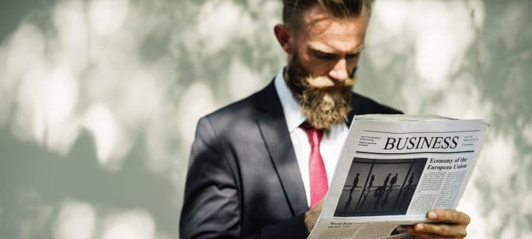 Hipster in suit reading a newspaper