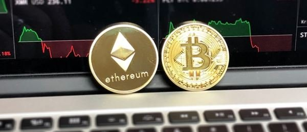 Bitcoin (BTC) and Ethereum (ETH) physical tokens lying against a laptop screen